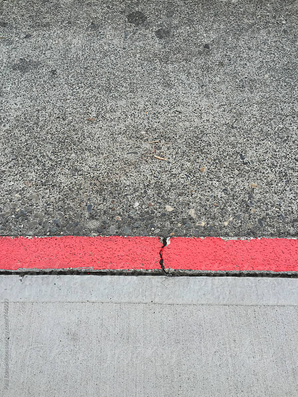 Painted red curb along urban sidewalk and street by Paul Edmondson for Stocksy United