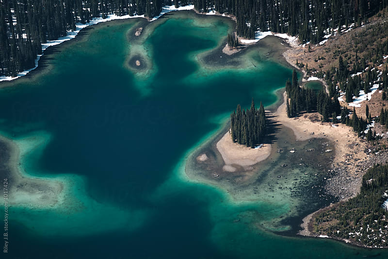 A grove of trees on a island in a emerald blue alpine lake by Riley Joseph for Stocksy United