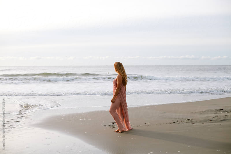 A woman stands on beach facing ocean by Jennifer Brister for Stocksy United