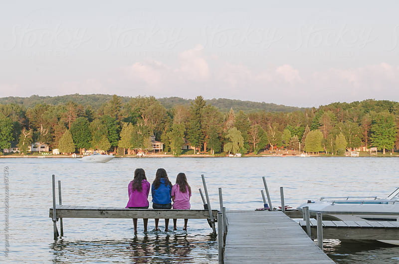 three young women sit at the end of a dock by Margaret Vincent for Stocksy United