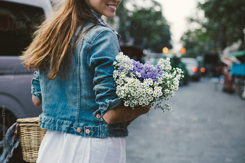 Girl holding a bouquet of wildflowers. by Jovo Jovanovic for Stocksy United