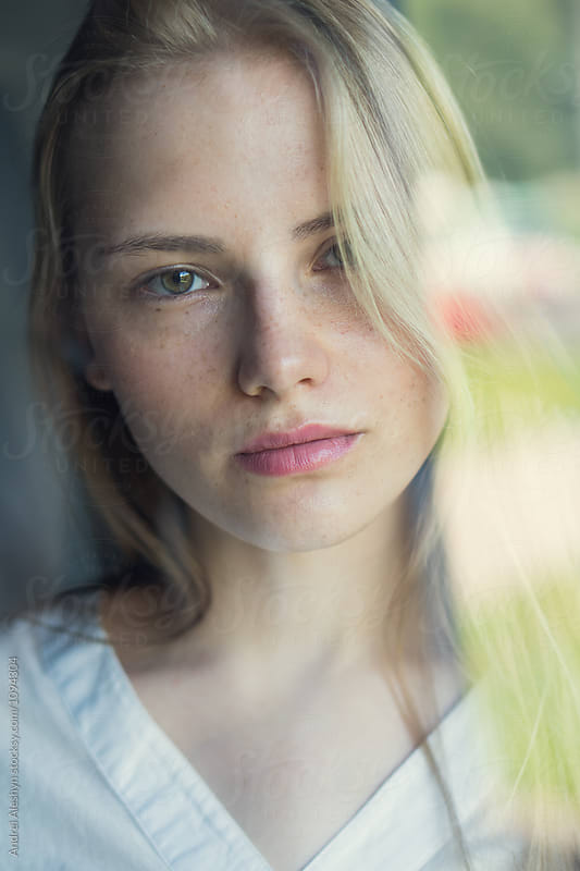 face of a beautiful young girl behind the glass by Andrei Aleshyn for Stocksy United