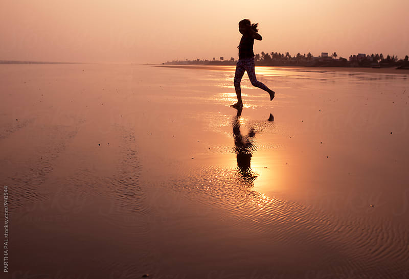 Girl running in sea beach at sunset time by PARTHA PAL for Stocksy United