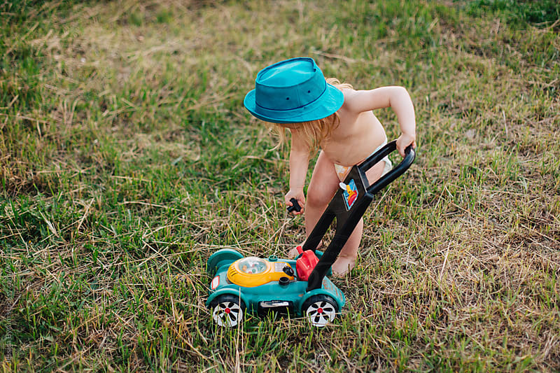 Toddler girl pull starting her mower by Jessica Byrum for Stocksy United