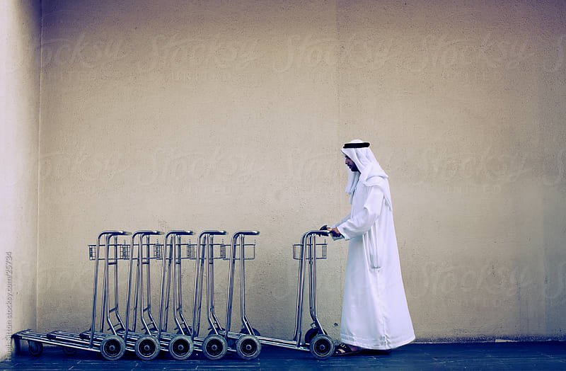 Arab collecting trolly at airport. Dubai by Hugh Sitton for Stocksy United