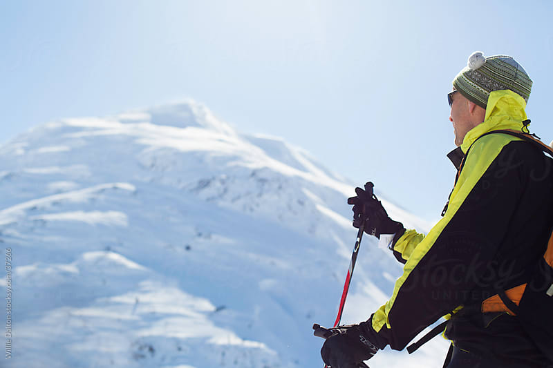 Man Dressed In Outdoor Apparel Looking Up at Wintery Mountain by Willie Dalton for Stocksy United