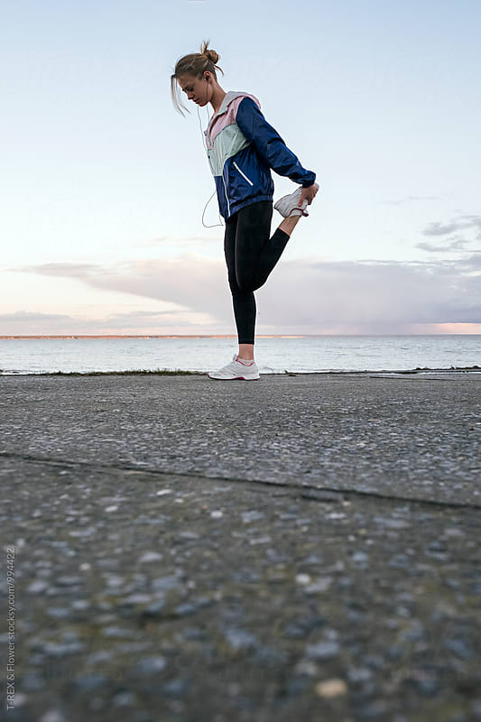 Sportswoman stretching on asphalt against of seascape by Danil Nevsky for Stocksy United