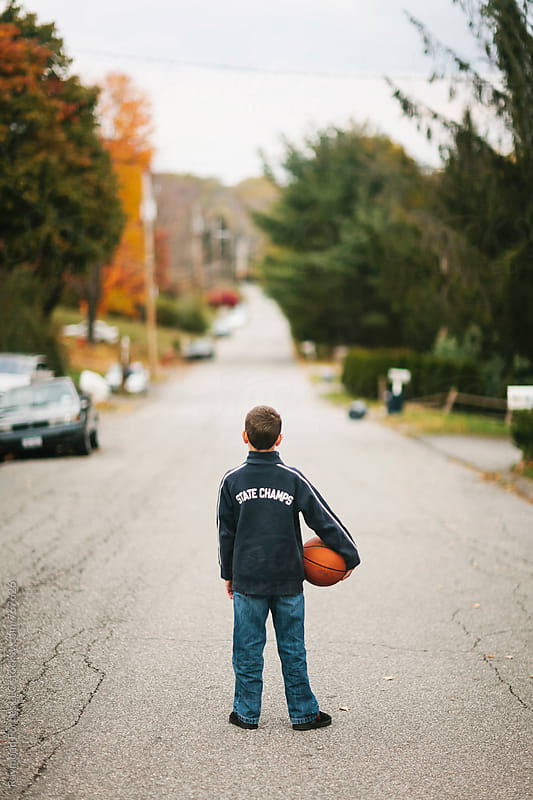 Portrait of Boy in Street with Basketball by Raymond Forbes LLC for Stocksy United