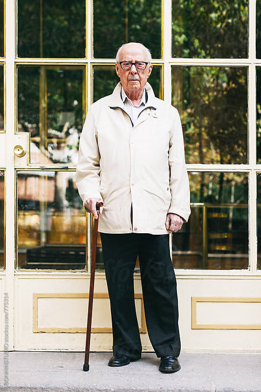 Portrait of an elderly man standing with a stick in front of a door. by BONNINSTUDIO for Stocksy United