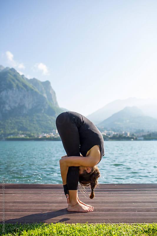 Woman doing yoga pose: Uttanasana by michela ravasio for Stocksy United