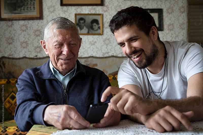Adult grandson showing to his granddad how to use the phone with touchscreen by Jovana Milanko for Stocksy United