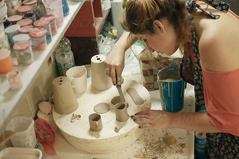 Young woman working alone on art project in ceramic studio by Nabi Tang for Stocksy United