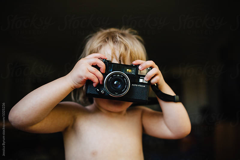 Toddler girl playing with an old camera. by Jessica Byrum for Stocksy United