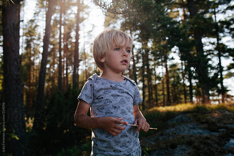 Boy looking at the view with a forest behind him. by Julia Forsman for Stocksy United