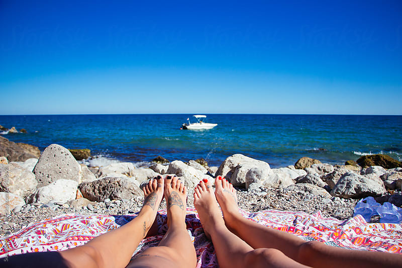 Feet of women on the beach sunbathing by Susana Ramírez for Stocksy United
