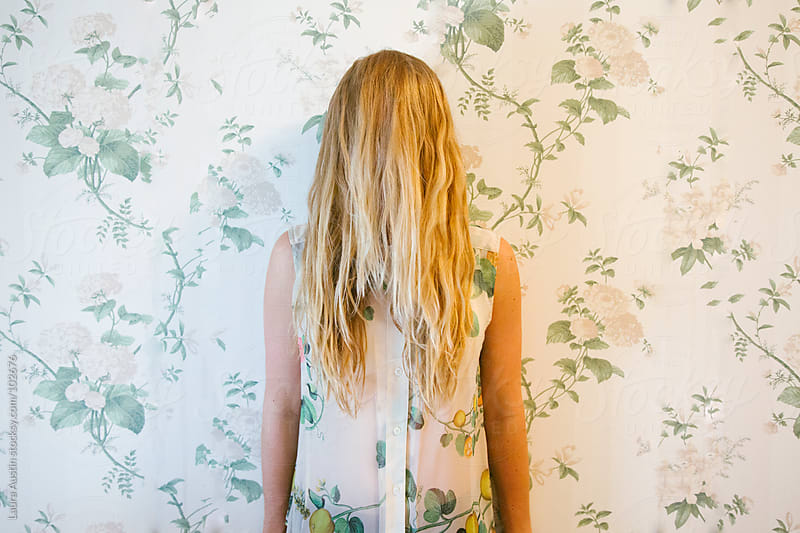 Blonde Girl Standing In Front Of Floral Wall With Floral Street by Laura Austin for Stocksy United