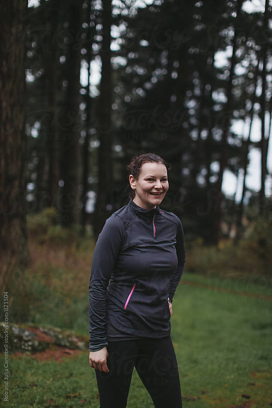 Middle age caucasian woman smiling outside after hard workout by Rob and Julia Campbell for Stocksy United
