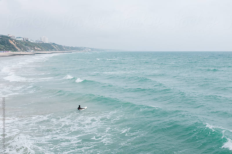 Man in a wetsuit leading a surfboard out to a stormy sea by Darren Seamark for Stocksy United