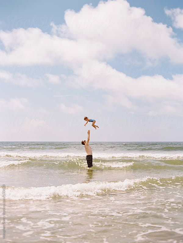 little girl playing at the ocean with her father by Meaghan Curry for Stocksy United