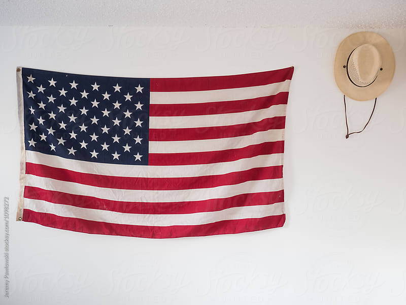 American flag and straw hat hanging on wall of bedroom as decoration by Jeremy Pawlowski for Stocksy United