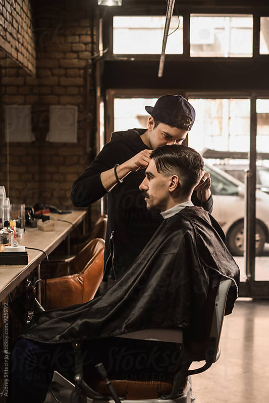 Young barber giving client a classic haircut in vintage barber shop by Marko Milanovic for Stocksy United