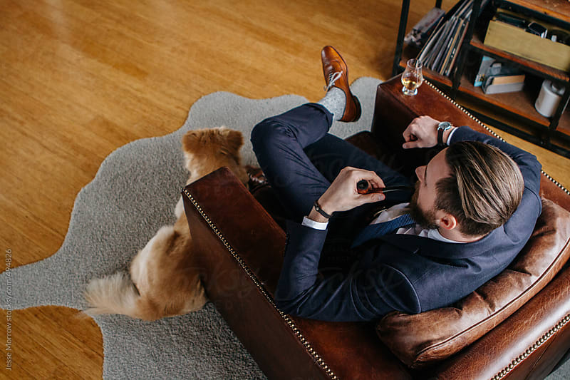 Young man in suit sits in leather chair smoking pipe with dog at feet  by Jesse Morrow for Stocksy United