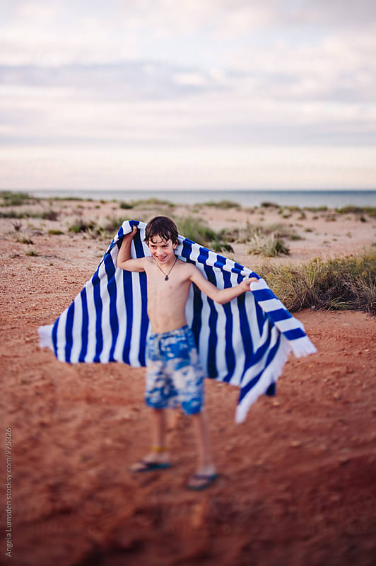 Boy in a bathing suit playing with a blue and white striped towel near a beach in Australia by Angela Lumsden for Stocksy United