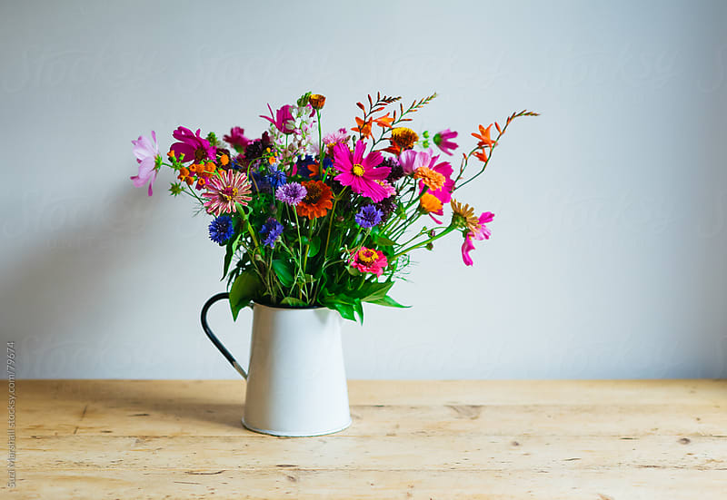 Flowers in a vase on a table by Suzi Marshall for Stocksy United