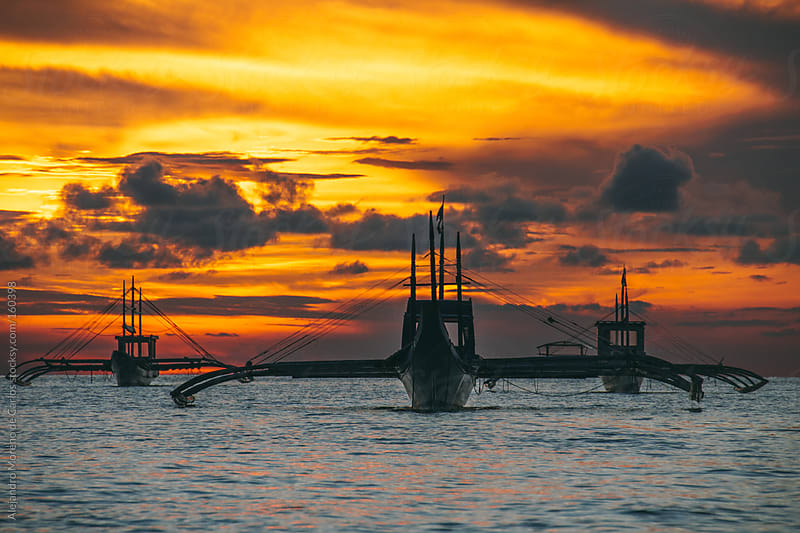 Traditional boats on the sea at sunset by Alejandro Moreno de Carlos for Stocksy United