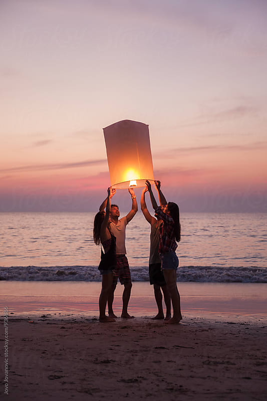 Group of friends releasing a lantern at the beach in Thailand by Jovo Jovanovic for Stocksy United