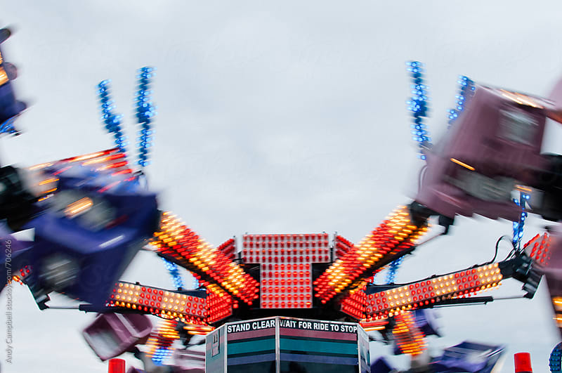 A carnival ride speeds past. by Andy Campbell for Stocksy United