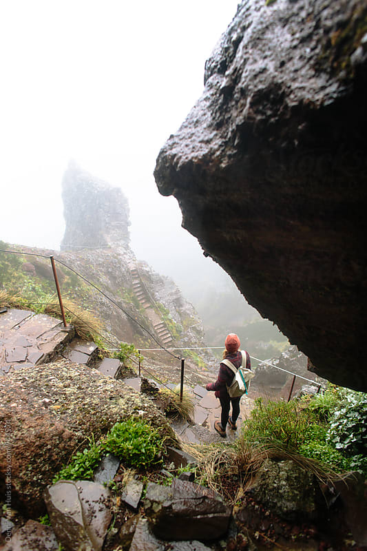 Brave woman walking down a  trail up in the mountains on a cloudy day by Denni Van Huis for Stocksy United