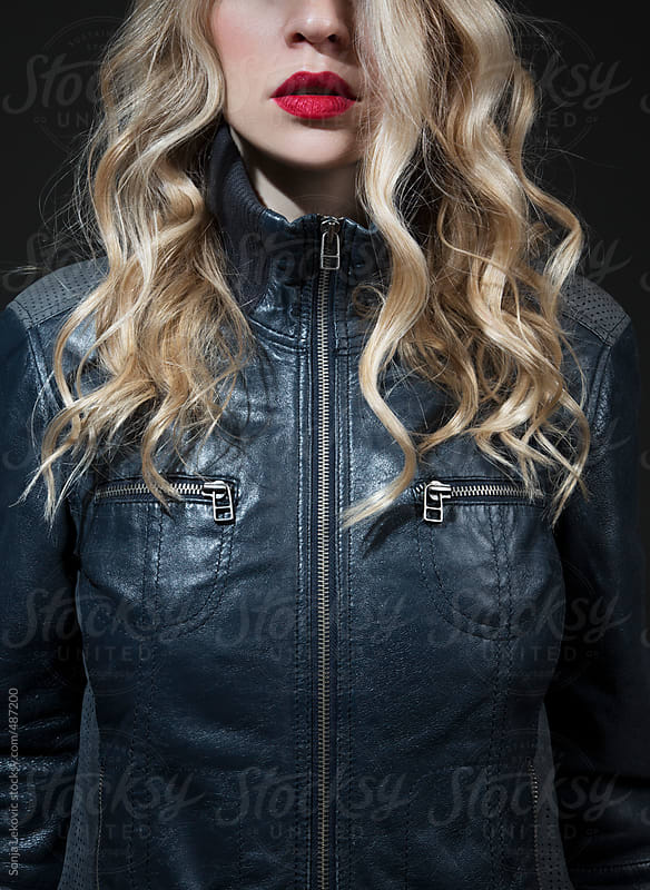 blond with red lipstick in a blue leather jacket by Sonja Lekovic for Stocksy United