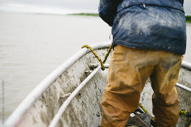 Fisherman throwing an anchor over a fishing boat by Kristine Weilert for Stocksy United