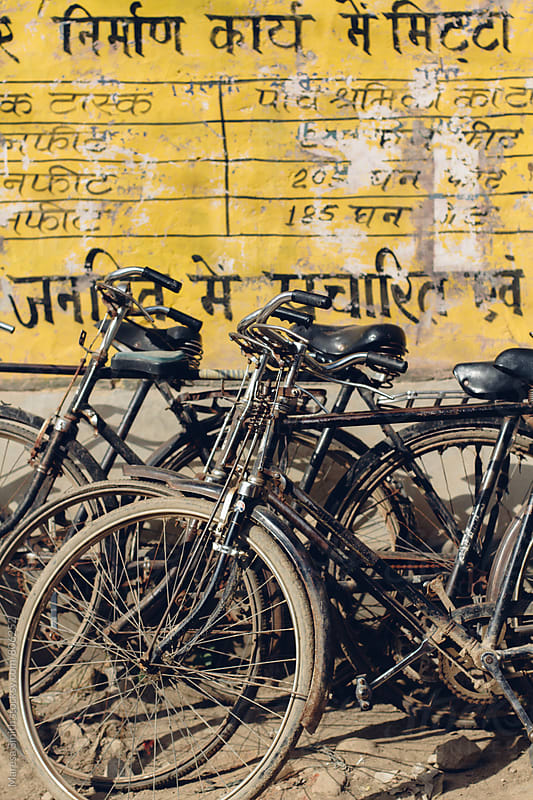 Dusty black bikes leaning on a yellow wall in India by Maresa Smith for Stocksy United