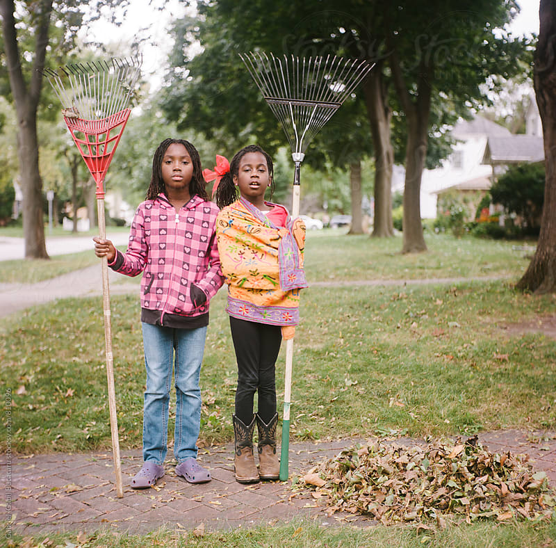Two African American girls holding rakes next to a leaf pile by Gabriel (Gabi) Bucataru for Stocksy United