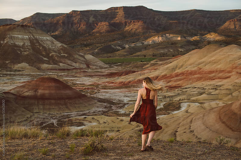 Young woman in red dress twirling around in the desert by Kate Daigneault for Stocksy United