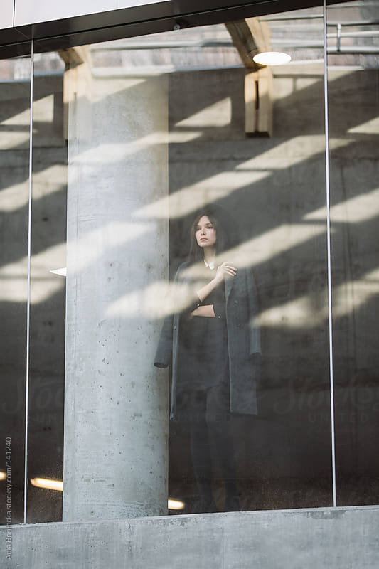 A mysterious woman standing behind a glass wall looking out into the street by Ania Boniecka for Stocksy United