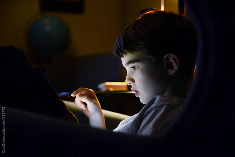 Profile of a child's face, lit by the screen of a tablet device he is working on by Cara Dolan for Stocksy United