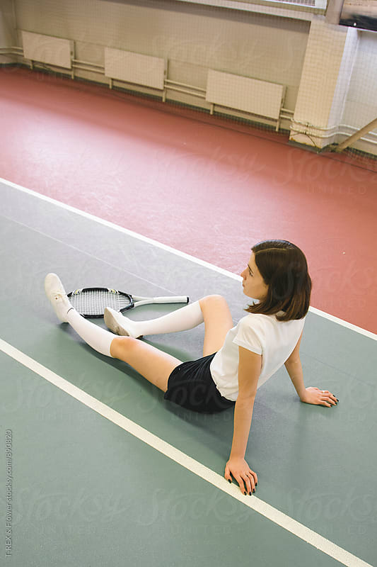 Side view of young woman sitting on tennis court indoors by Danil Nevsky for Stocksy United