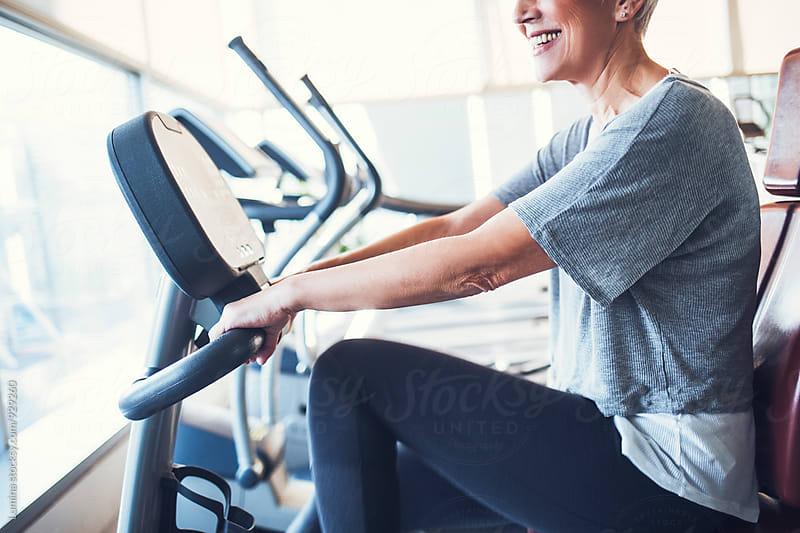 Woman Working Out on a Bicycle at Gym by Lumina for Stocksy United