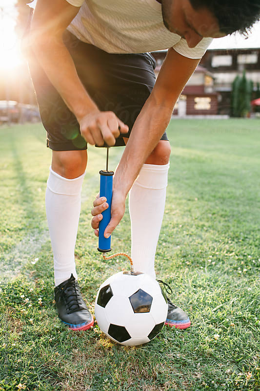 Football player pumping ball by Ani Dimi for Stocksy United