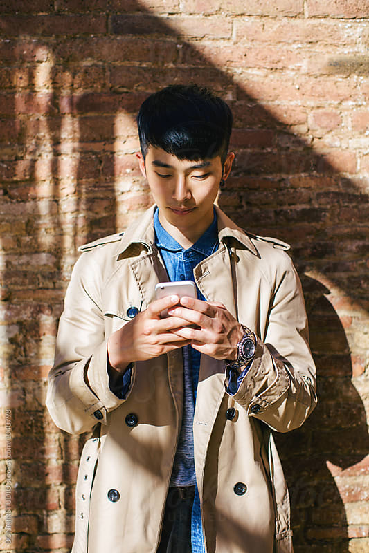 Young asian businessman using mobile phone outdoors. by BONNINSTUDIO for Stocksy United
