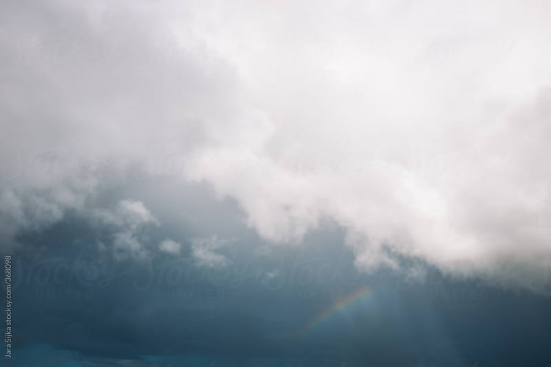 Small part of rainbow in clouds by Jara Sijka for Stocksy United