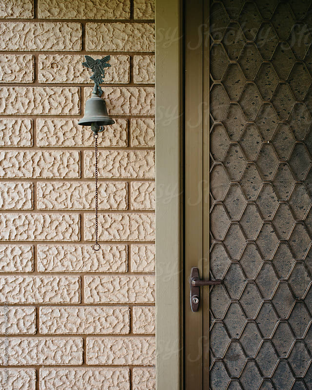 Security screen and door bell by Robert Lang for Stocksy United