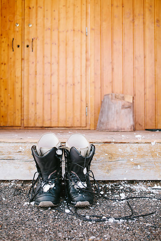 Male snowboard boots covered with snow standing in front of a porch by Ivo de Bruijn for Stocksy United
