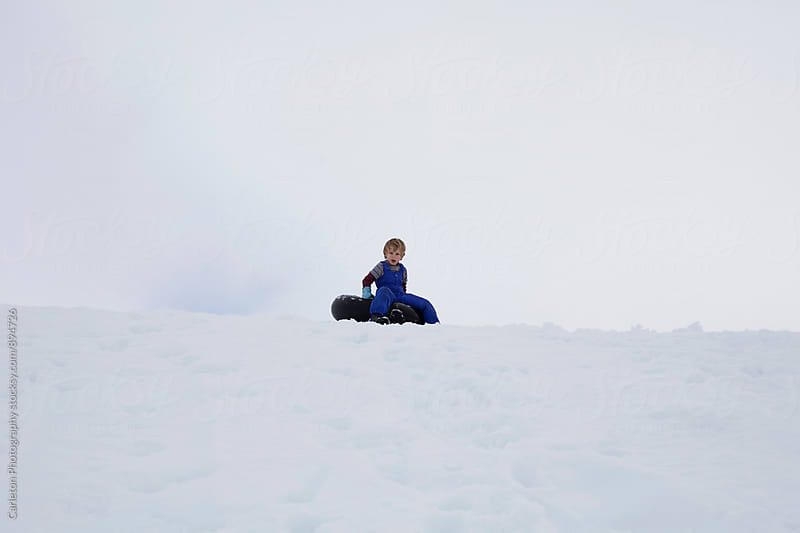 Boy sits on inner tube on top of a snowy hill, getting ready to go by Carleton Photography for Stocksy United
