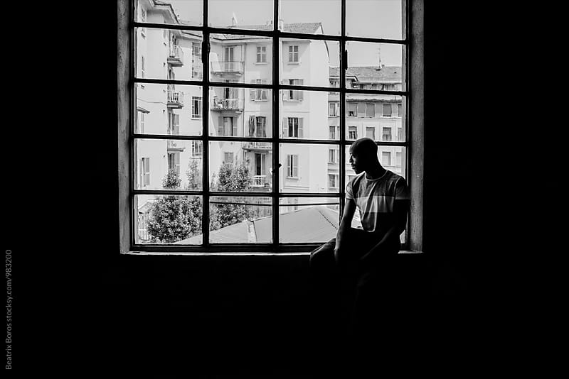 Black and white photo of a man in front of a big window by Beatrix Boros for Stocksy United