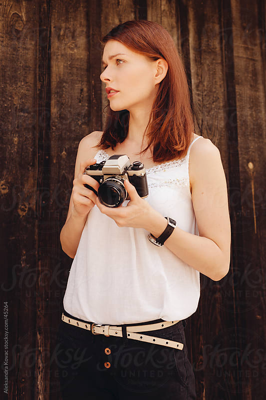 Young woman holding a analog camera and standing  in front of a wooden wall by Aleksandra Kovac for Stocksy United
