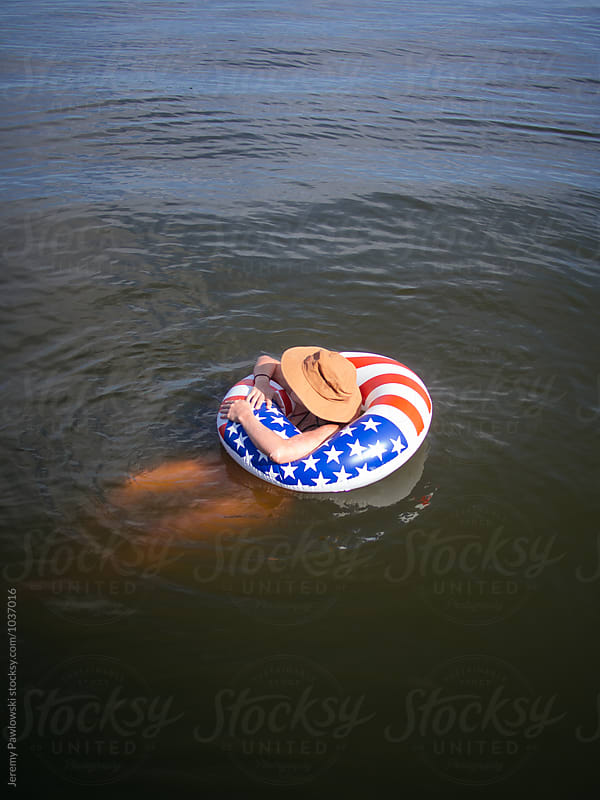 Girl in American Flag float wearing hat looking out at lake by Jeremy Pawlowski for Stocksy United